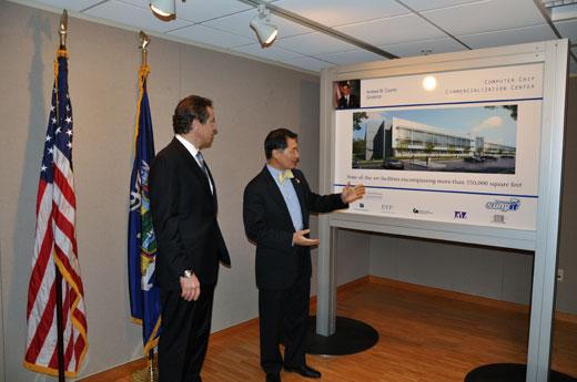 2 men in suites looking at building rendering