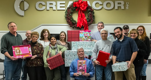 Employees gathered holding presents
