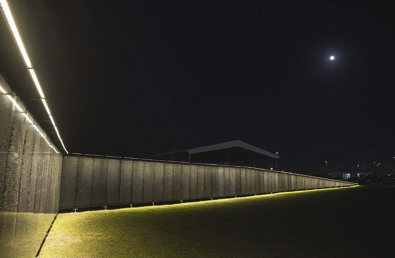 Vietnam Veterans Memorial wall lit up at night