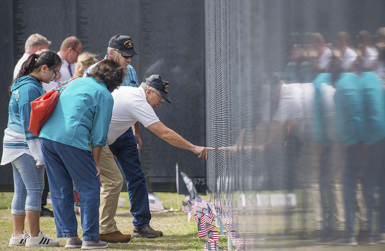 Man points to name on Vietnam Veterans Memorial wall