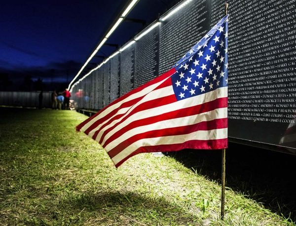 American Flag in front of memorial wall