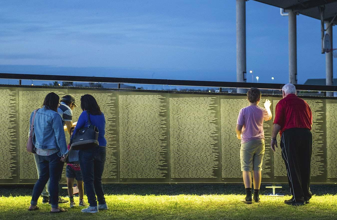 people looking at names on Vietnam Veterans Memorial Wall