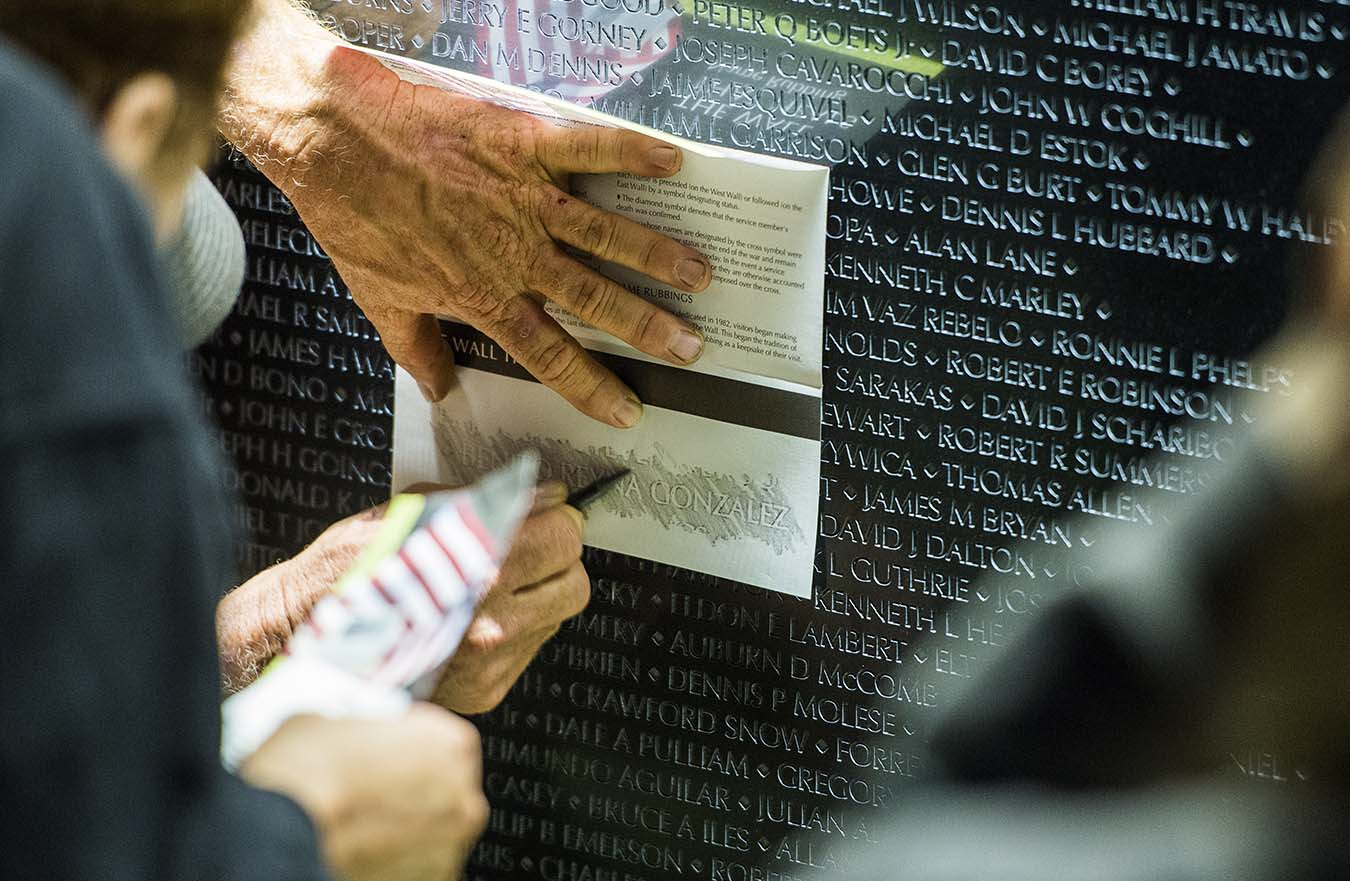 person tracing name on wall