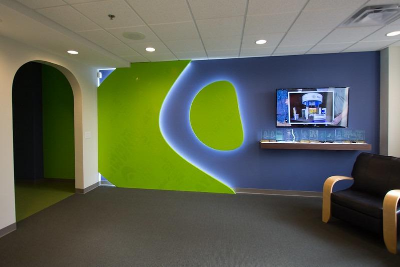 large logo design backlit on wall with shelf for awards