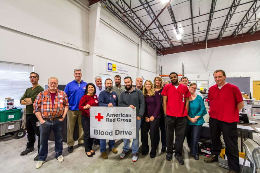 creatcor staff holding american red cross blood drive banner